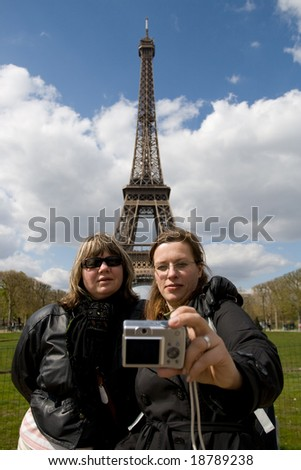 Group of tourists taking self portrait at the famous Eiffel tower in Paris - stock photo