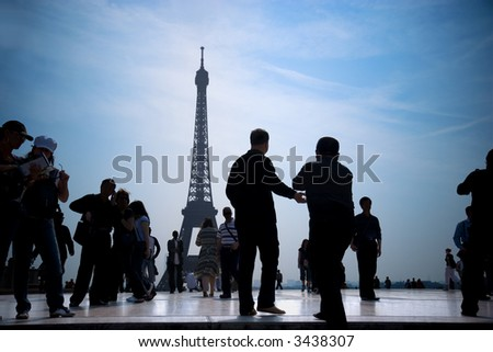 Group of tourists walking and taking pictures of Eiffel Tower. - stock photo