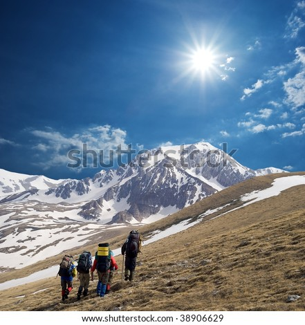 group of tourists walking in a mountains - stock photo