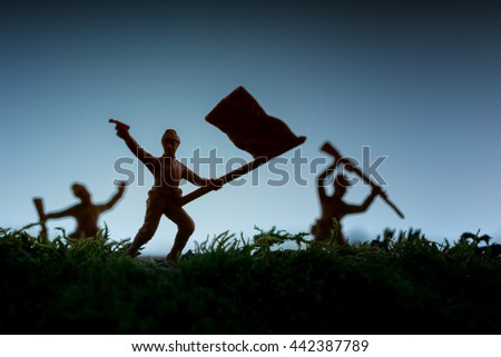 Group of toy soldiers attacking and carrying the flag - stock photo