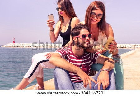 Group of travel friends having fun with mobile technology at ferry pier - Cheerful teenagers using phone sitting by ocean - University students on vacation for the spring break -Soft vintage filter - stock photo