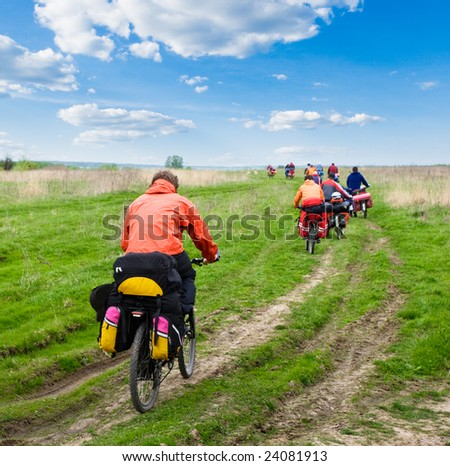 Group of traveling cyclists crossing the field - stock photo