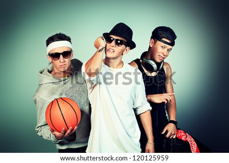 Group of trendy teenagers posing at studio. - stock photo