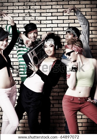 Group of trendy teenagers posing together against a brick wall. - stock photo