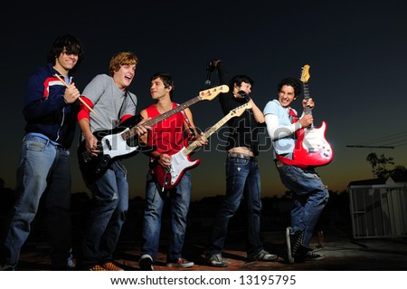Group of trendy teenagers with musical instruments - stock photo