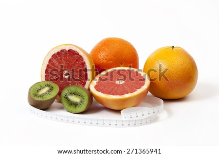 Group of tropical fruits and tape measure in centimeters around, shooted over white - stock photo