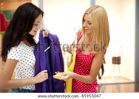 Group of two beautiful shopping women trying on clothes at shopping mall indoors