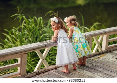 Group of two cute little flower girl in the beautiful garden - stock photo