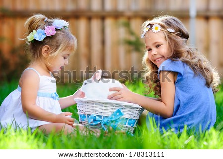 group of two little girl with a bunny rabbit have a easter at green grass background - stock photo