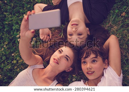 Group of two young woman and child lying on the grass and taking selfie - stock photo