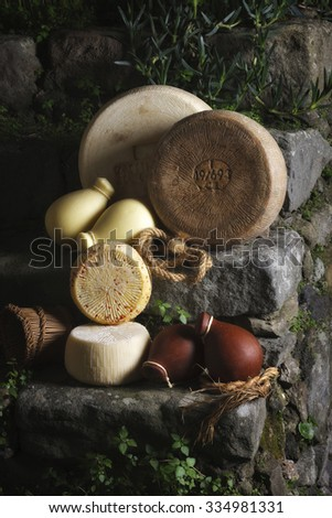 Group of typical sicilian cheeses on a stone staircase - stock photo