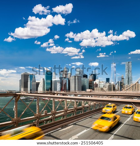 Group of typical yellow New York cabs on the Brooklyn bridge with Lower Manhattan - stock photo