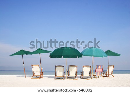 Group of umbrellas and sun beds on the beach - stock photo
