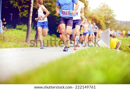 Group of unidentified marathon racers running, detail on legs - stock photo