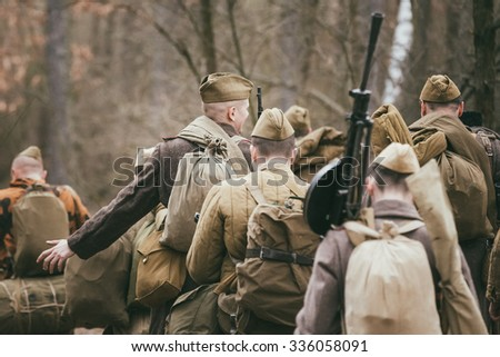Group of unidentified re-enactors dressed as Russian Soviet soldiers in camouflage walks through forest. - stock photo