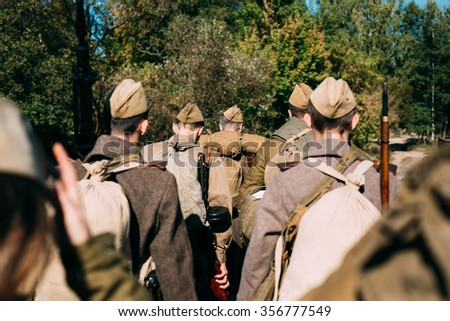 Group of unidentified re-enactors dressed as Soviet russian soldiers goes along a forest road. - stock photo