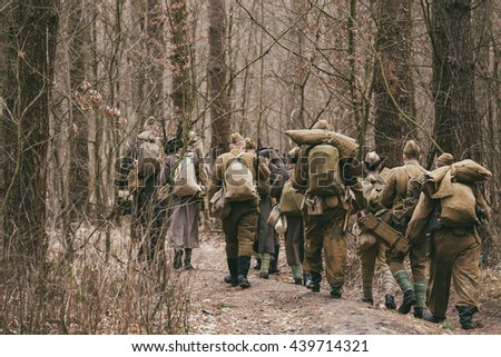 Group Of Unidentified Re-enactors Dressed As World War II Russian Soviet Soldiers In Camouflage Walks Through Forest. - stock photo