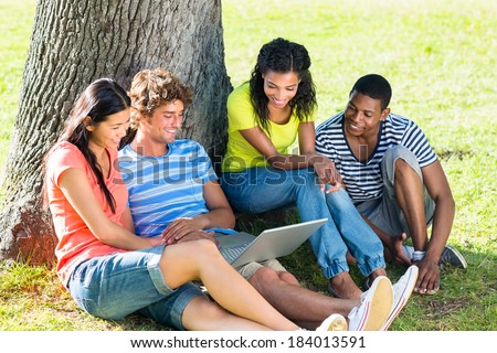 Group of university students using laptop together on college campus