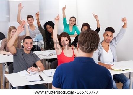 Group of university students with hands raised answering teacher in classroom