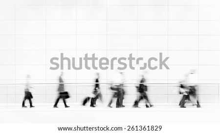 Group of unrecognizable business people in front of modern architecture, blurred motion, monochrome photo