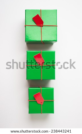 Group of various sizes green color gift boxes arranged in a row. Bird eye view. - stock photo