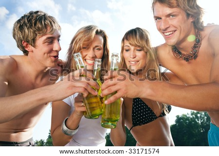 Group of very beautiful people celebrating on the beach in the summer of their lives - focus on faces - stock photo