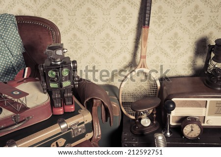 Group of vintage assorted items on attic hardwood floor with vintage wallpaper background. - stock photo