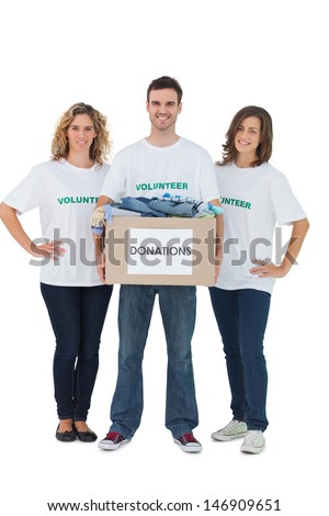 Group of volunteers holding donation box with clothes on white background - stock photo