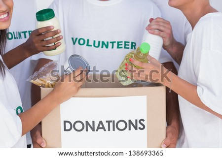 Group of volunteers putting food in donation box - stock photo