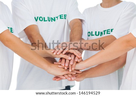 Group of volunteers putting hands together on white background - stock photo