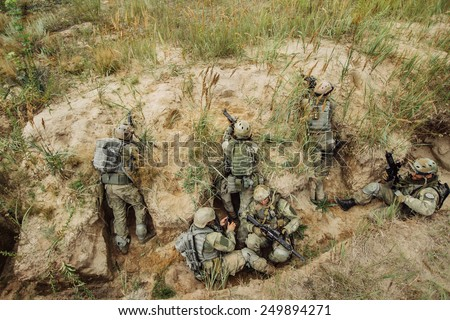 group of warriors hiding in the trenches and firing - stock photo