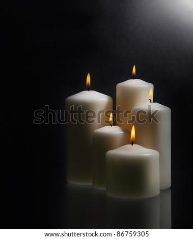 Group of white burning candles over black background - stock photo