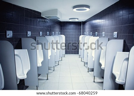 group of white porcelain urinals in public toilets photo