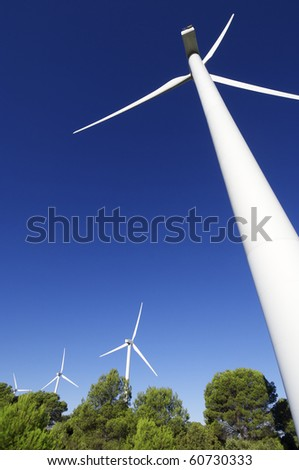group of wind turbines in a wooded area - stock photo