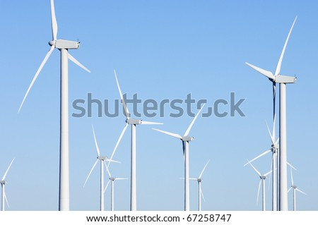 group of windmills for electricity production with clear and blue sky - stock photo