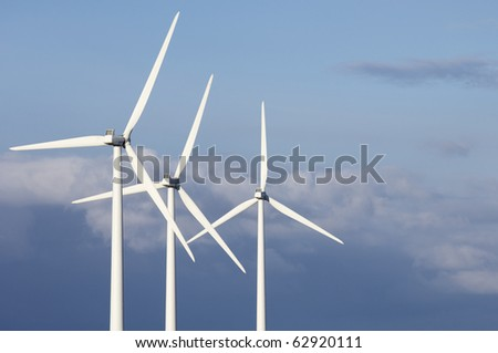group of windmills for electricity production with stormy sky - stock photo