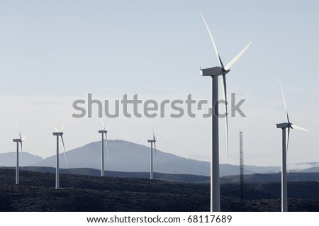 group of windmills for power generation in a landscape with hills - stock photo