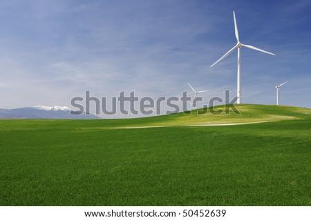 group of windmills in an idyllic green meadows - stock photo