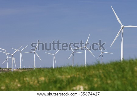 group of windmills looming in a green meadow grass - stock photo