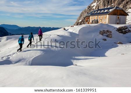 Group of winter hikers approaching alpine hut in Dachstein region, Austria - stock photo