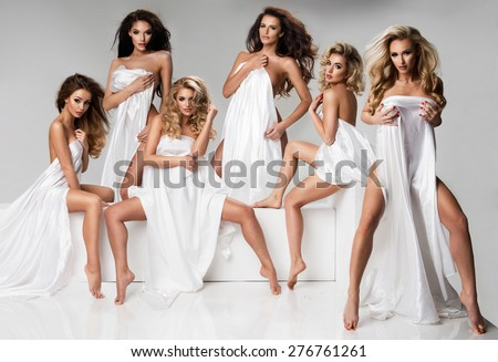 Group of woman wear only white material in studio - stock photo