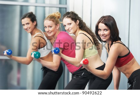 group of woman with dumbbells in gym at fitness physical training exercise in sport wear - stock photo
