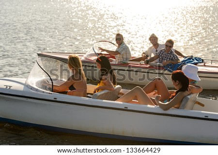 Group of women and men navigating motorboats summer lake - stock photo