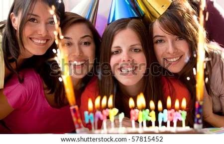 Group of women at a birthday party having fun and holding the cake