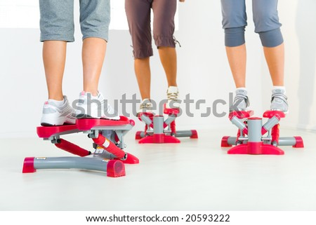 Group of women doing exercise on stepper. Closeup on legs. Low angle view. - stock photo