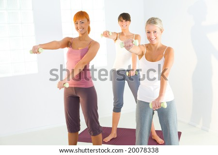 Group of women doing fitness exercise with dumbbells on mat. They're looking at camera. - stock photo