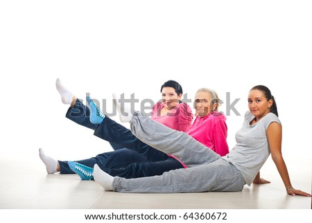 Group of women doing sport  while sitting on floor and lifting their legs - stock photo