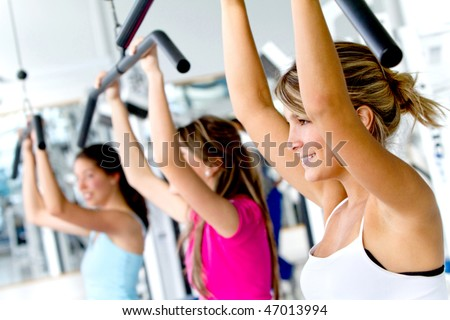 Group of women exercising with the machines at the gym - stock photo