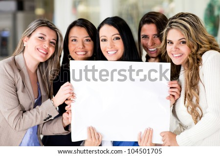 Group of women holding a banner ad and smiling - stock photo