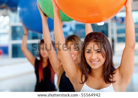 Group of women in a pilates class at the gym with a ball - stock photo